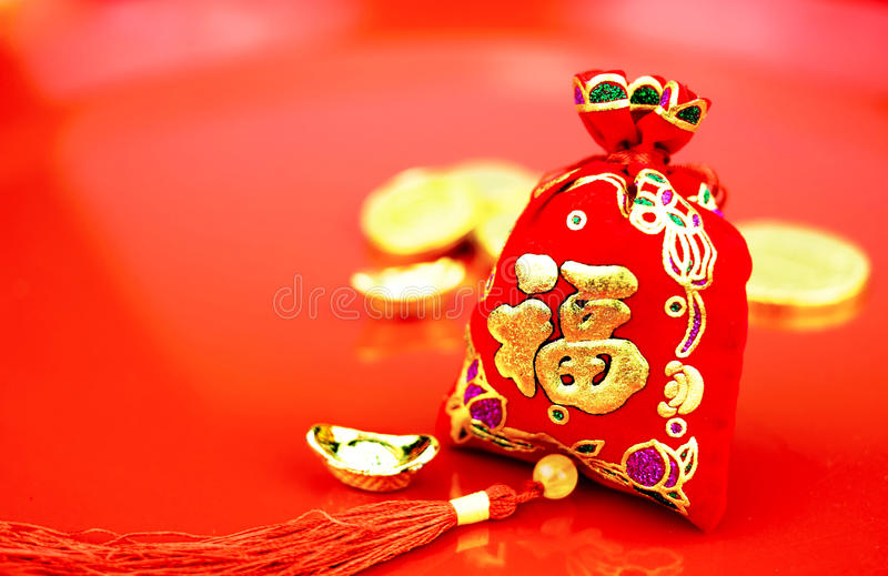 Chinese new year decoration: red felt fabric bag or ang pow with. Word prosperous and golden ingots on red glossy floor royalty free stock images