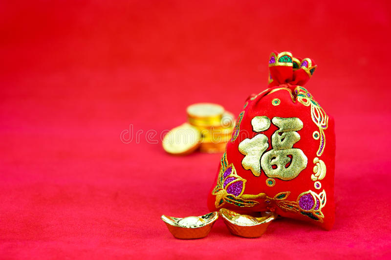 Chinese new year decoration: red felt fabric packet or ang pow w. Ith word prosperous and golden ingots on red fabric stock images