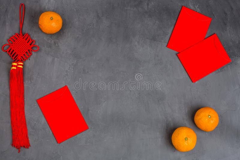 Chinese New Year decoration with tangerines and red envelopes on gray concrete background. Happy Chinese new year 2020 festival royalty free stock image