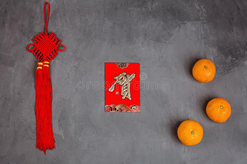 Chinese New Year decoration with tangerines and red envelopes on gray concrete background. Happy Chinese new year 2020 festival. stock images