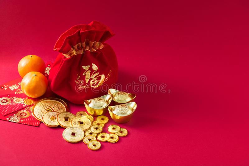 Chinese new year decorations, money bag, Orange, Gold Coins with character meaning, good luck, riches, healthy, honour, happiness. On red background royalty free stock image