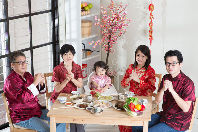 Chinese New Year Family Reunion Dinner. Happy Chinese New Year, reunion dinner. Happy Asian Chinese multi generation family with red cheongsam greeting while stock images