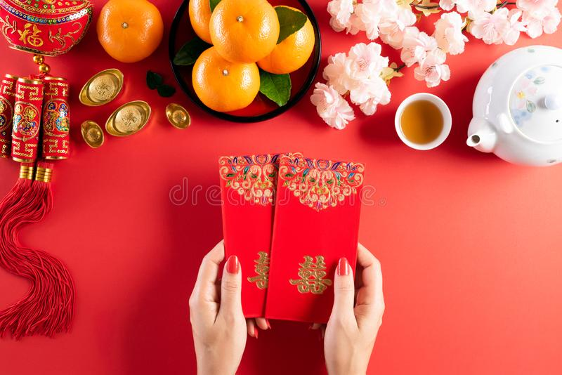 Chinese new year festival decorations. Woman hand holding pow or red packet, orange and gold ingots on a red background. Chinese. Characters FU means fortune royalty free stock image