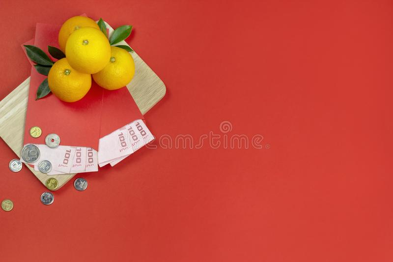 Chinese new year fresh oranges and angpao pocket with wooden board on red paper background stock photo