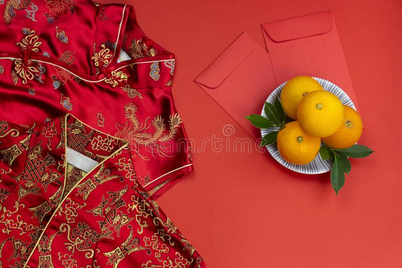 Chinese new year fresh oranges and angpao pocket and qipao on red paper background royalty free stock photos