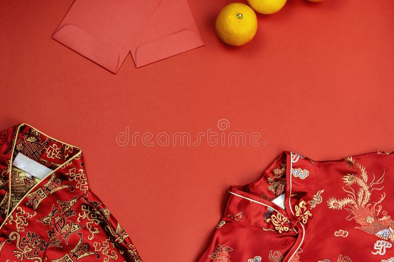 Chinese new year fresh oranges and angpao pocket and qipao on red paper background stock photography