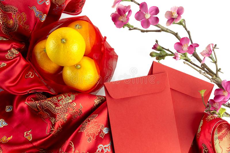 Chinese new year fresh oranges and Angpao pockets on red Chinese fabric and cherry blossom branch border on white background stock photo