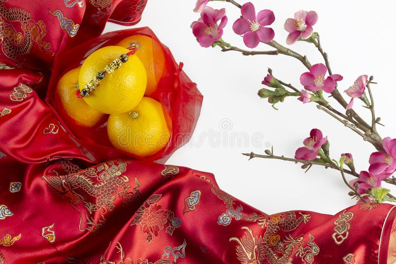 Chinese new year fresh oranges on red Chinese fabric and cherry blossom branch border on white background stock image