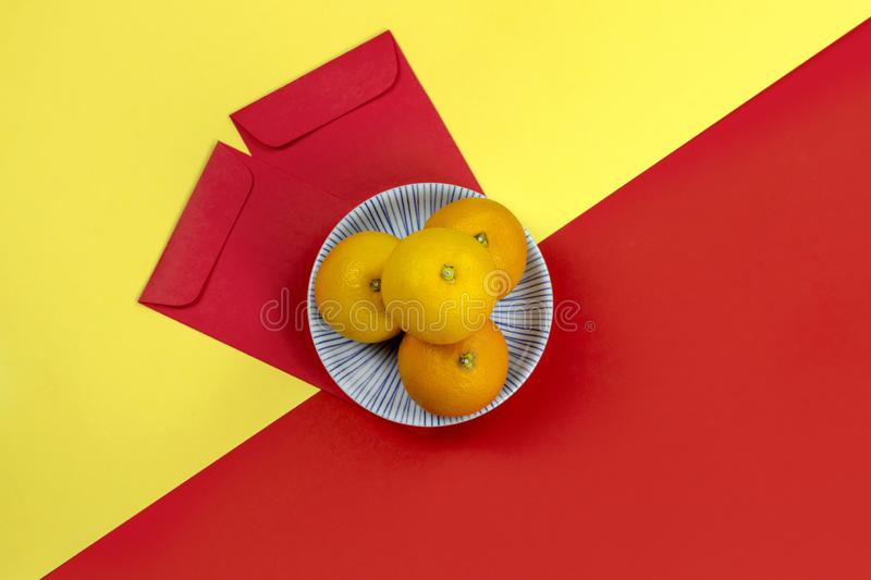 Chinese new year oranges and red angpao pocket on bright yellow and red paper background stock photography