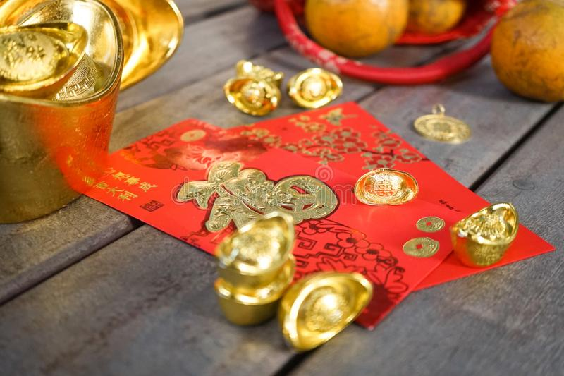 Chinese New Year ornaments with oranges, gold ingots and red envelopes or hong pao on wood background. Selective focus. Chinese stock photo