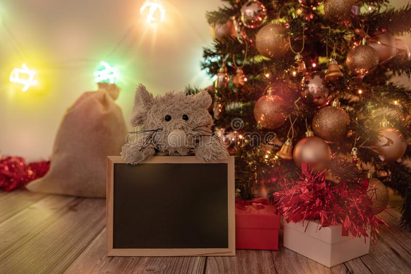 Chinese New Year of the rat. Decorated Christmas and New Year tree on a wooden table, with glowing balls on the background. Presents and decorations. Chinese New royalty free stock photography