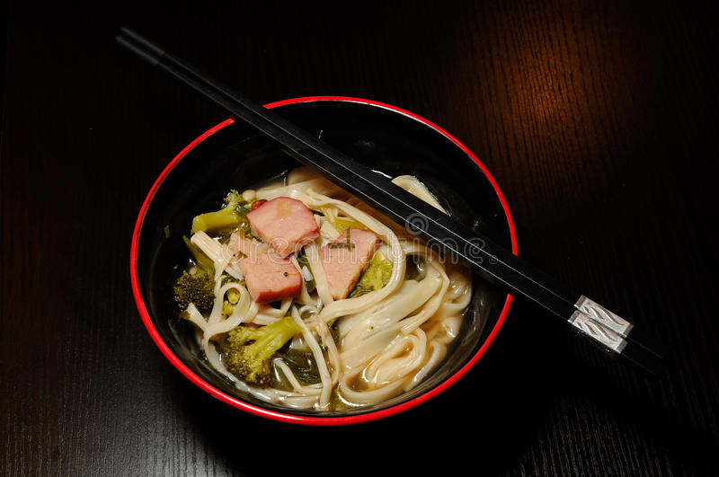 Chinese Noodle Dinner. A bowl of noodles, broccoli, mushrooms and pork slices. Chopsticks are resting on the bowl