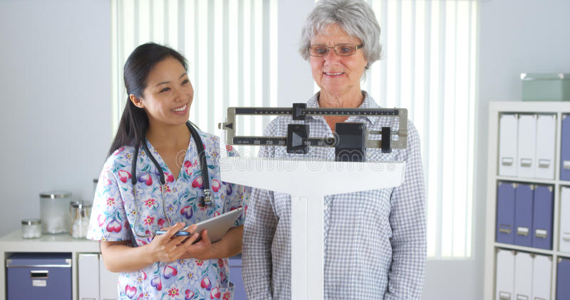Chinese nurse weighing elderly patient. In the office stock image