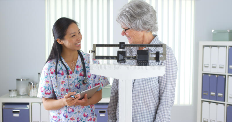 Chinese nurse weighing elderly patient royalty free stock image