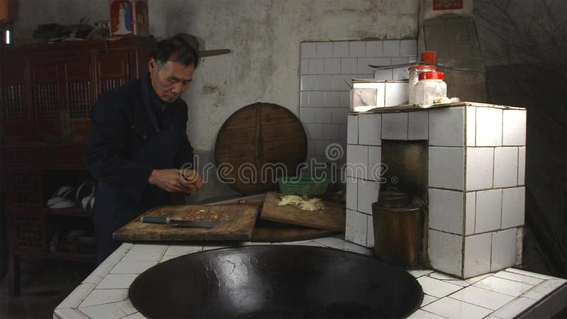 Chinese old man cooking in kitchen at his home countryside. Yunnan. China. royalty free stock image