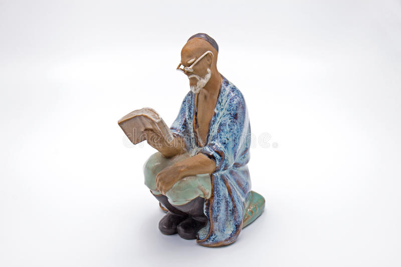 Chinese Old Man Reading Book Statue on White Background stock photography
