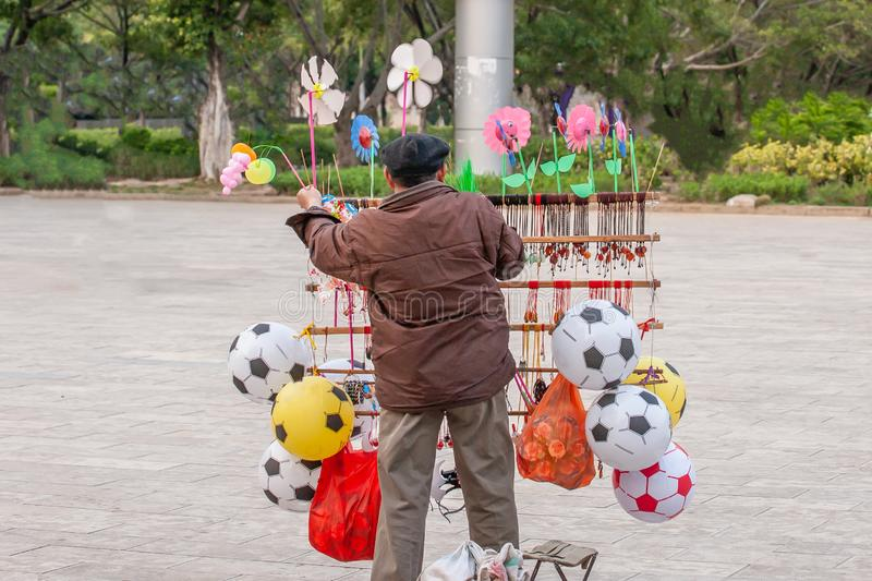 Chinese old man street vendor seller ball and other toys in the Public garden, Nansa, Yunnan, China. Football concept royalty free stock photo