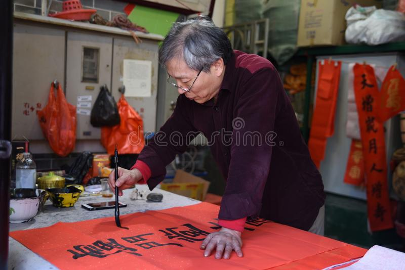 A Chinese old man is writing calligraphy stock images