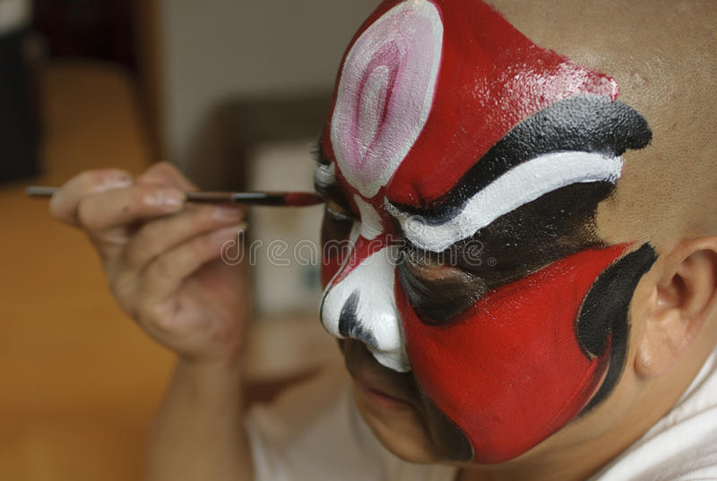 A chinese opera actor is painting his face royalty free stock photo