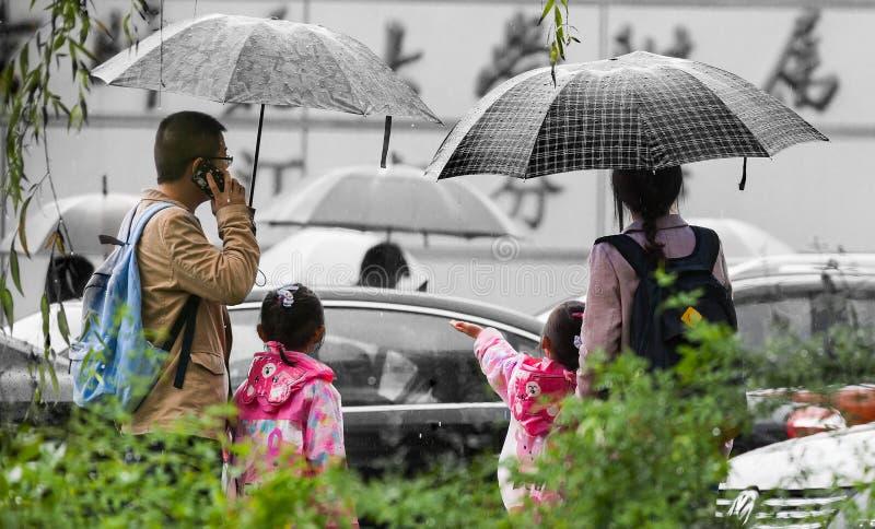 Chinese ouders die hun kinderen na school opnemen stock foto