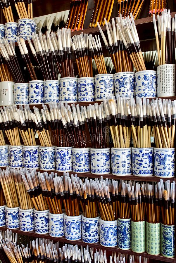 Chinese paint brushes and brushes for calligraphy in cups stand in rows on shelves. patterns with dragons on ceramic cups royalty free stock image