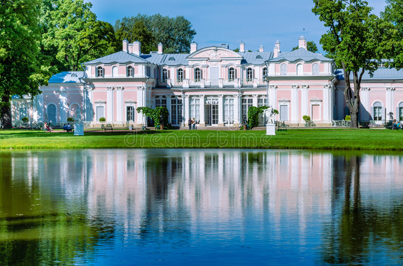 Chinese Palace on the shore of the pond in the Park of Oranienbaum, near St. Petersburg. Chinese Palace on the shore reflected in the blue water of a pond stock photos
