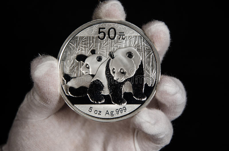 Chinese Panda Silver Coin White Glove. This Chinese Panda 5 oz silver coin was shot on a black background & being hand held with a white glove stock photo