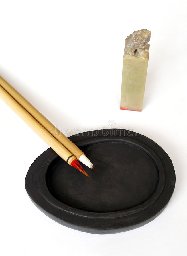 Chinese pen on ink stone. An ancient type chinese calligraphy or painting brush, placed on a black stone slab for grinding ink. Taken on clean white background royalty free stock photo