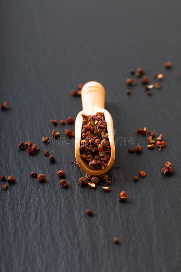 Chinese peppercorn, Sichuan pepper in wooden scoop on black slate stone plate with copy space royalty free stock photo