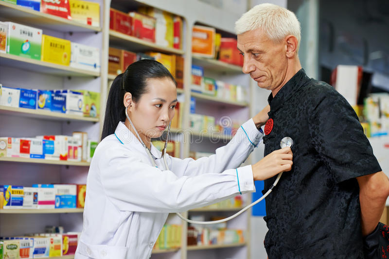Chinese pharmacy woman with patient royalty free stock photos