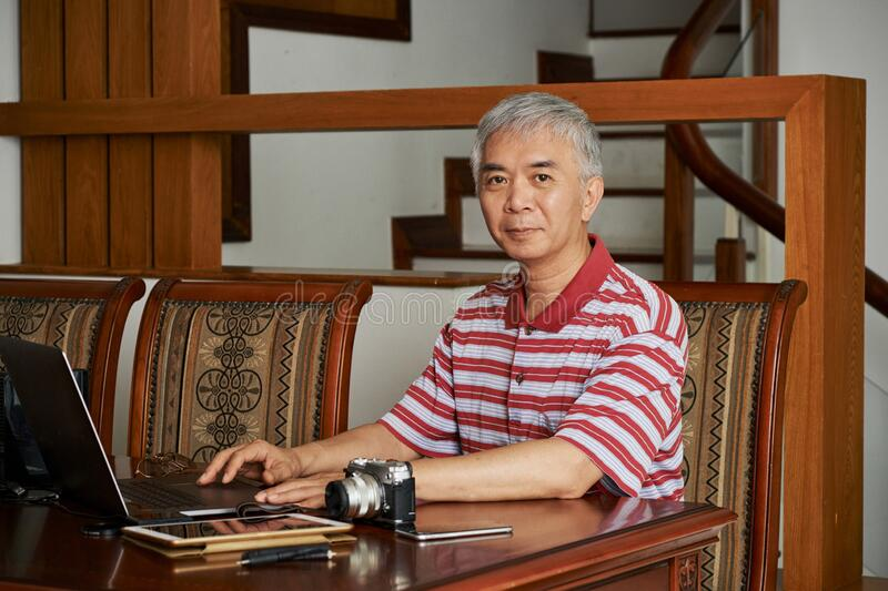 Chinese photographer working on laptop royalty free stock photo