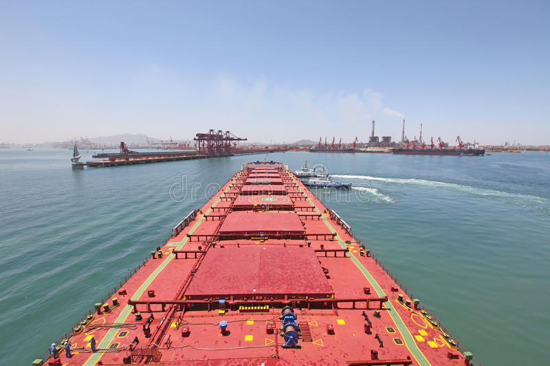 Into the Chinese port of Qingdao ore carriers royalty free stock photography