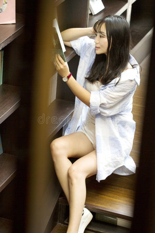 Chinese Portrait of young beautiful woman reads Book In Bookstore. Reading with concentration royalty free stock image