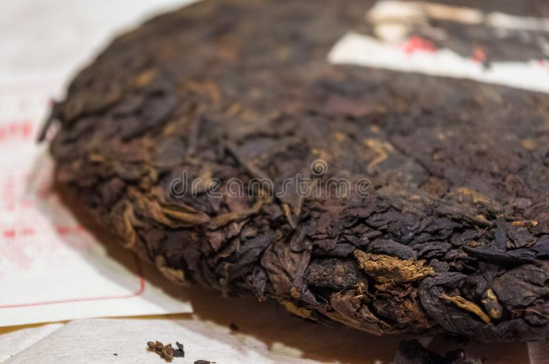 Chinese pressed puer tea on wrapping paper, close-up, macro. Chinese pressed puer tea on wrapping paper, close up, macro royalty free stock image