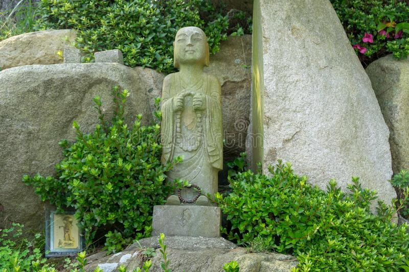Chinese priest stone sculpture in the garden of Haedong Yonggungsa Temple stock photography