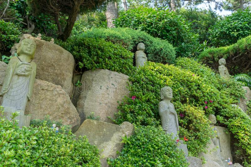 Chinese priest stone sculptures in the garden of Haedong Yonggungsa Temple. BUSAN, SOUTH KOREA - JULY 20, 2017 : Chinese priest stone sculptures in the garden of royalty free stock photography