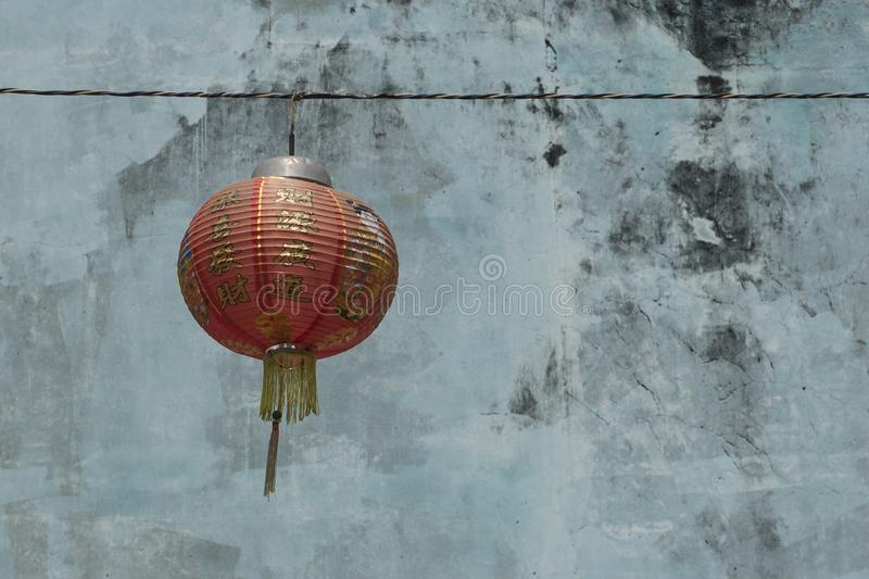 Chinese red paper lantern hangs on a string with a weathered painted outside wall on the background royalty free stock photo