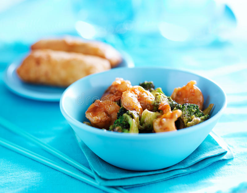 Chinese shrimp stir fry. In colorful table setting stock images