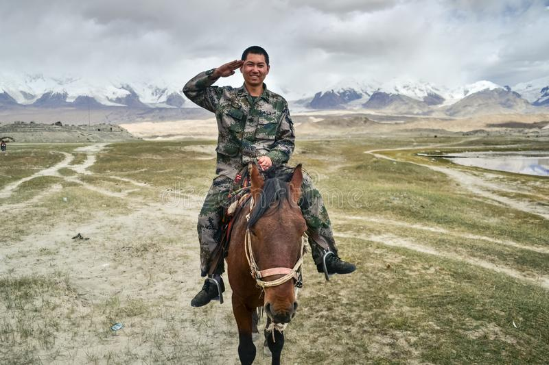 Chinese soldier riding a horse near Karakul Lake salutes to camera, China stock photo
