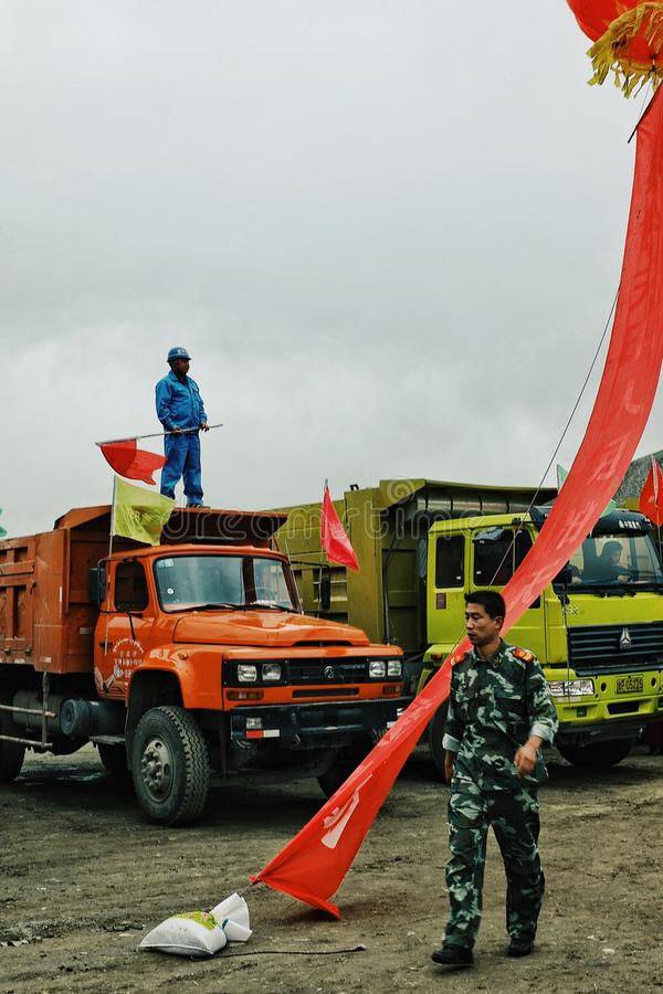 chinese soldier walking past by some heavy duty trucks with a worker on top waving the national red flag stock image