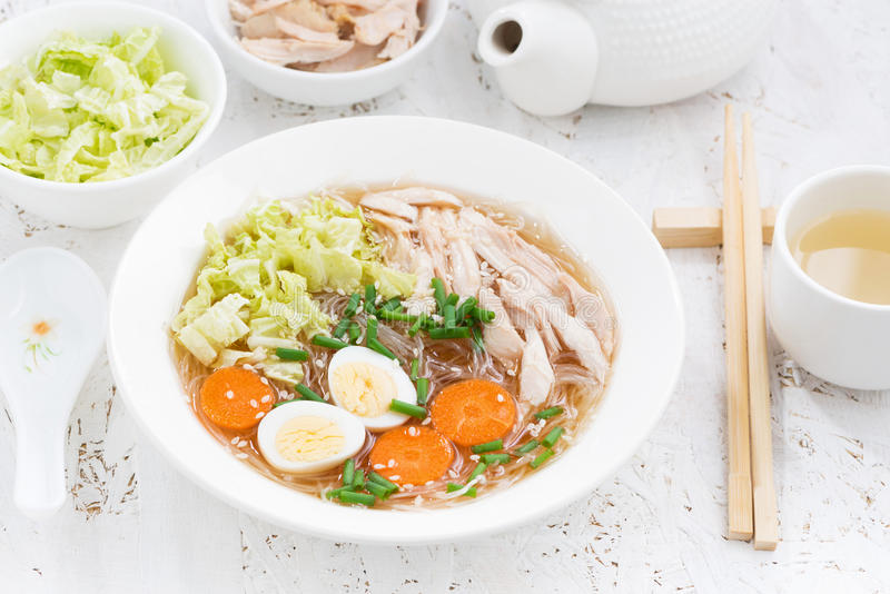 Chinese soup with glass noodles, vegetables and chicken. On white table, closeup stock photos