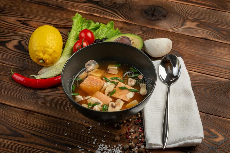 Chinese soup with red fish in a black plate on a wooden background stock image