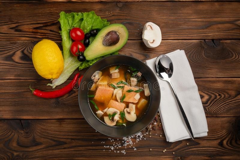 Chinese soup with red fish in a black plate on a wooden background royalty free stock photo