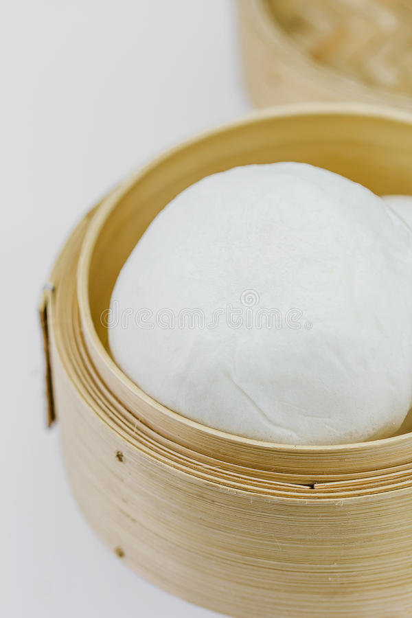 Chinese steamed bun in bamboo ware. On white background royalty free stock image