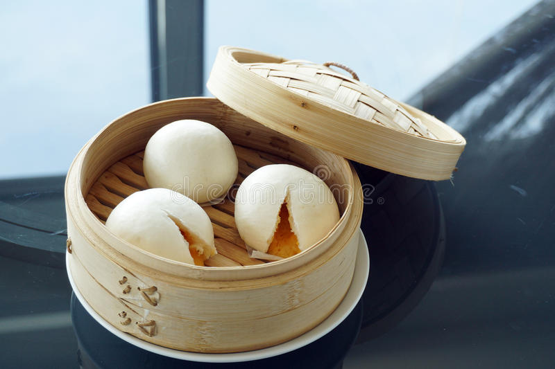 Chinese steamed bun. Or Chinese steamed yolk custard lava bun in bamboo tray - Traditional Chinese dim sum, Selective Focus royalty free stock photos