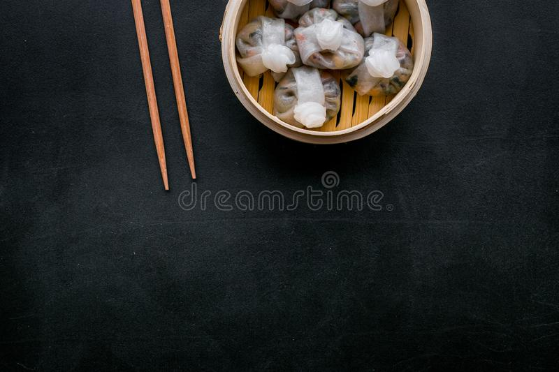 Chinese steamed dumplings Dim Sum in bamboo steamer on black background top view mock up. Chinese steamed dumplings Dim Sum in bamboo steamer on black table stock photo