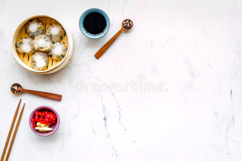 Chinese steamed dumplings Dim Sum with sweet paper and spices in bamboo steamer on marble background top view mock up royalty free stock image