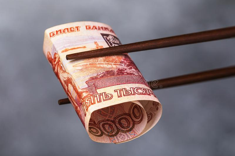 Chinese sticks hold five thousand rubles. The concept on the relationship between Russia and China royalty free stock image