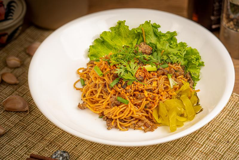 Chinese stir fried noodle. With pork on white dish royalty free stock photo