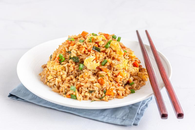 Chinese Stir Fried Rice with Chopsticks. Chinese Stir Fried Rice with Eggs and Vegetable on White Plate on White Background Horizontal Photo royalty free stock photos